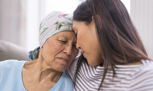 A patient with a terminal illness, who is wearing a headscarf, being comforted by another person