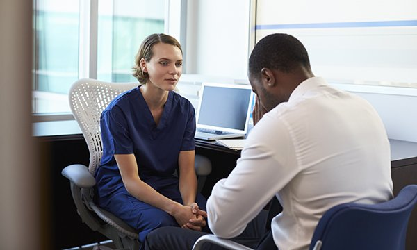 Picture shows a doctor in a consultation with a man who appears to be upset.  By walking in the shoes of carers whose loved ones are dying, teams of nurses are finding ways to improve support offered by their hospitals.