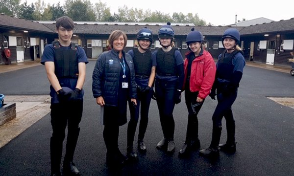 Picture of nurse Sharon Mott with trainee jockeys and grooms at the British Racing School. She took on a challenge in agreeing to create a role in which she is responsible for the health and well-being of the trainees.