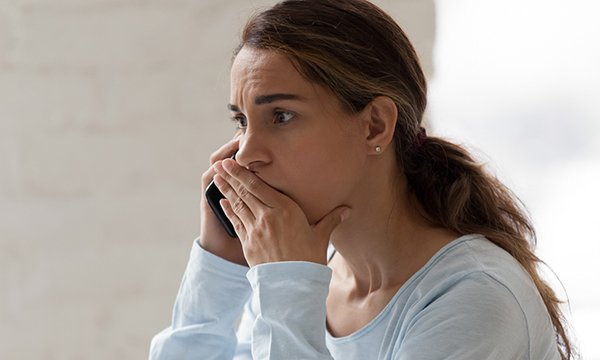 Picture shows a woman looking anxious and speaking on a phone. Two mental health trusts in London have set up round the clock mental health emergency departments that patients in crisis can reach by phone during the pandemic.
