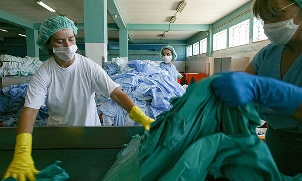 Picture shows workers wearing masks in a hospital laundry