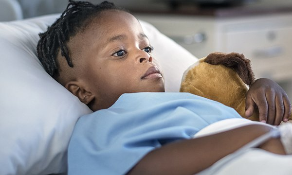 Picture shows a young black boy lying in a hospital bed, clutching a toy