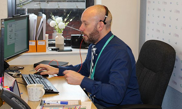 Picture shows Peter Grace, clinical lead for the digital health team, taking a call. A video link is enabling nurses to triage older people in care and nursing homes, avoiding unnecessary admissions to the emergency department.