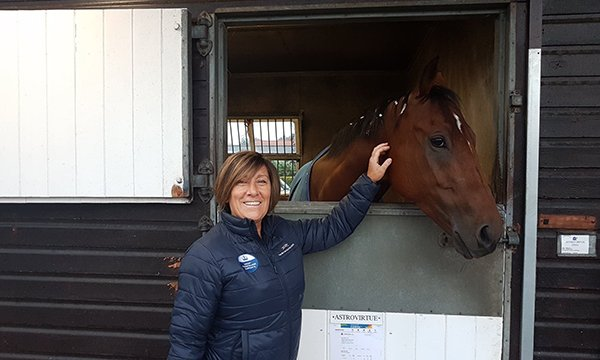 Picture of nurse Sharon Mott with a horse at the British Racing School. She took on a challenge in agreeing to create a role in which she is responsible for health and well-being of young would-be jockeys and grooms at the school.