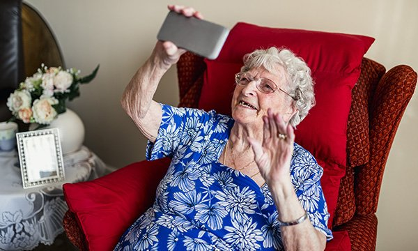 An older woman using a smartphone in a care home