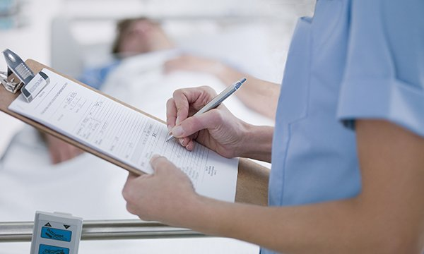 Picture shows nurse keeping records. This article offers advice on how to make documenting your work easier