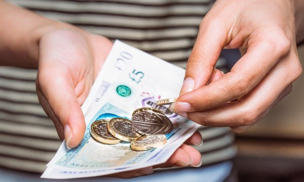 Picture shows someone counting cash. The article says nurses need to learn about personal health budgets, which allow patients to use NHS funding to purchase care outside traditionally commissioned services.