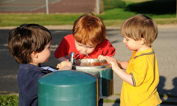Picture shows boys taking turns drinking from a water fountain at a park. Practical information aimed at schools, nurseries and colleges to support children with bladder and bowel issues and toileting has been published by Bowel and Bladder UK.
