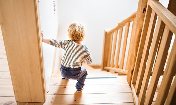 Child at top of stairs may fall. The Royal Society for the Prevention of Accidents wants to reduce such injuries and save lives