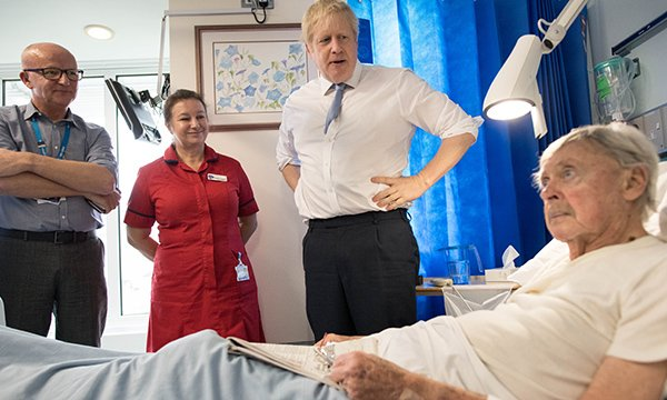 Prime minister Boris Johnson speaking to a patient on a ward, accompanied by healthcare staff