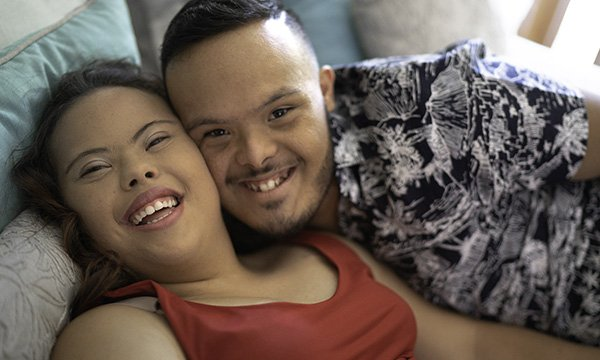 Picture shows a couple with learning disabilities smiling at the camera. Dating agencies for people with learning disabilities aim to help them find not only romance but also friendships that can reduce social isolation.