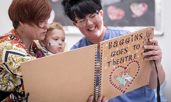 Picture of healthcare assistant Lisa Morgan reading a story to a young patient about a fictional bear going to the operating theatre. She has improved the care of children facing cardiac surgery through a training package for staff and other initiatives.