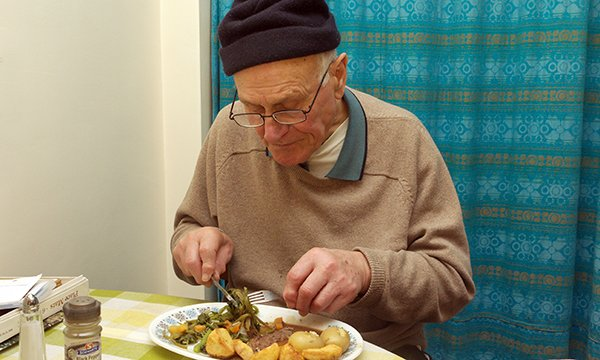 Older person tucks into a roast meal. Unexpected weight loss in older people should not be ignored