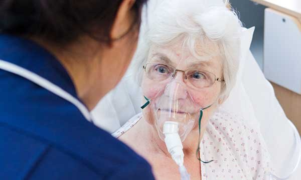 Picture shows an older woman in bed, wearing an oxygen mask, talking to a medic. Lorraine Creech describes the challenges facing the charity supporting people with mesothelioma