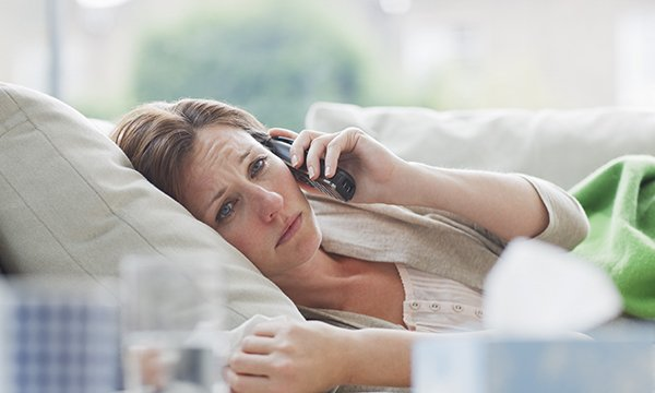 A woman lying in bed, looking visibly distressed and talking on the phone.