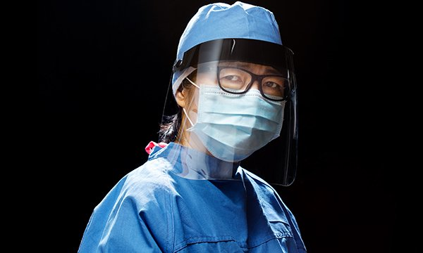 A nurse in PPE, wearing a visor, mask and gown