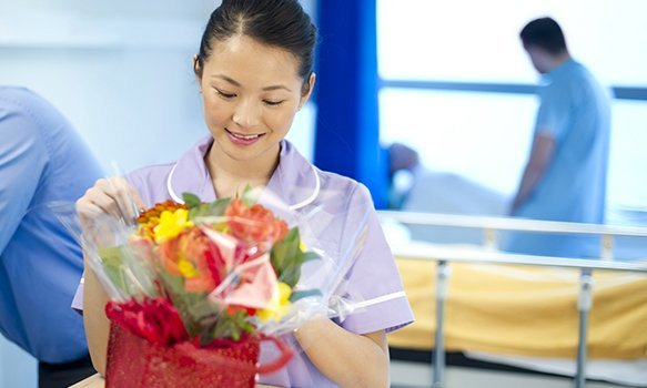 A nurse on a ward receiving a patient's gift of flowers