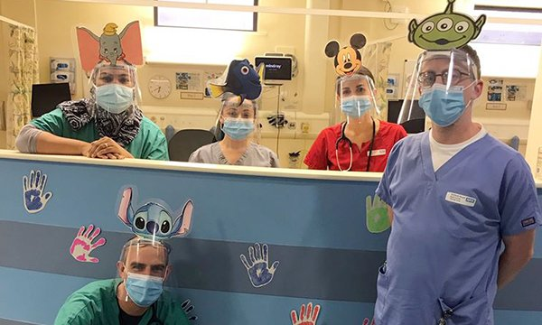 Picture shows medics at Salford Royal Hospital's paediatric emergency assessment unit wearing cartoon cut-outs on their protective visors