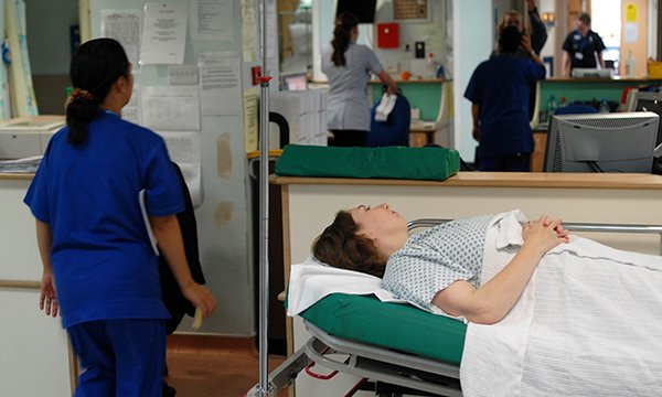 Picture shows a nurse standing next to a woman lying on a trolley in a hospital corridor. The official NHS count of 12-hour waits at emergency d­­epartments in England underestimates the actual figure, says the Royal College of Emergency Medicine.