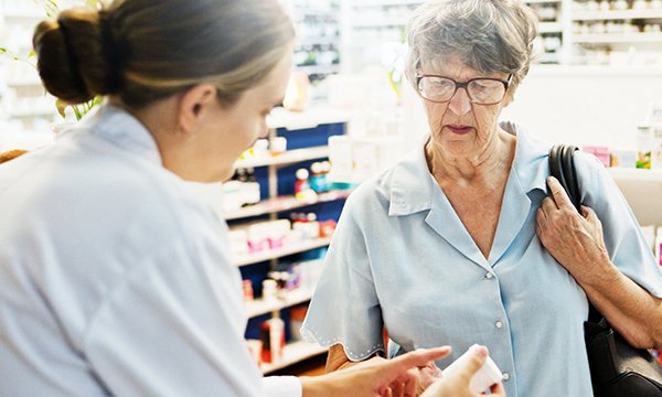 Picture shows pharmacist explaining medication to an older woman.