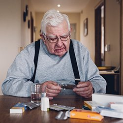 Picture shows an older man sitting at a table examining one of numerous packages of medicines set out in front of him. Many older people are on multiple prescription medicines, putting them at risk of side potentially serious effects.