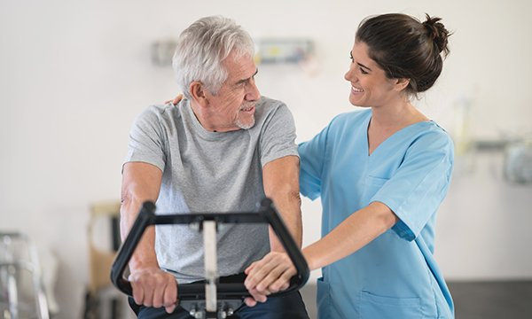 Picture shows a female physiotherapist with an older male patient who is on a static bicycle. Evidence shows that physical exercise has a positive effect on patients before, during and after treatment.