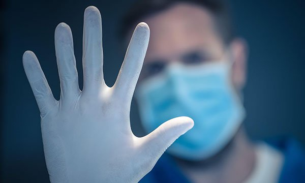 Picture of a medic wearing a mask and holding up his hand, wearing a glove, in a 'stop' gesture.