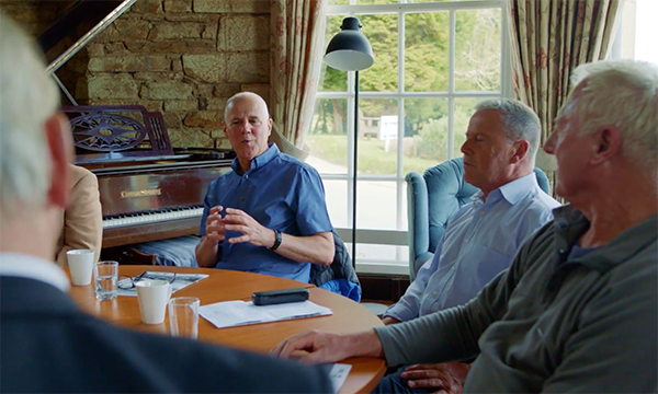 Picture shows a group of older men sitting round a table holding a discussion. This is a workshop for prostate cancer patients run as part of the supported self-management programme. New care pathways are easing the strain on prostate cancer services.