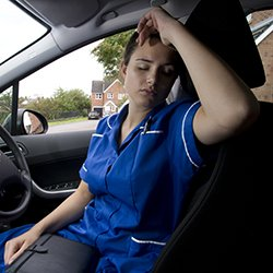 Picture shows model depicting an exhausted nurse resting in her car. The RCN says the number of community nurses fell 3% in 2014-18.