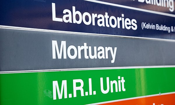 Picture shows a hospital sign with directions including the mortuary. By walking in the shoes of carers whose loved ones are dying, teams of nurses are finding ways to improve support offered by their hospitals.