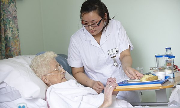 Picture of a nursing student caring for an older patient