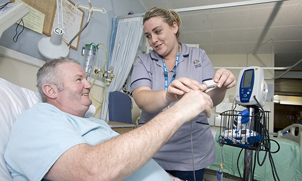 A nursing student helping a patient on a hospital ward