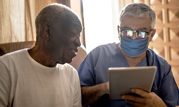 Picture shows a medic holding a pad, talking to an older black man. Older men and black men are more at risk of prostate cancer.