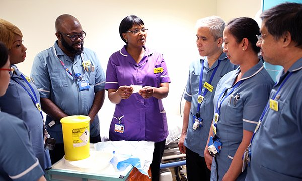 Nurse innovator Taurai Matare shows a colleague around a piece of scanning equipment