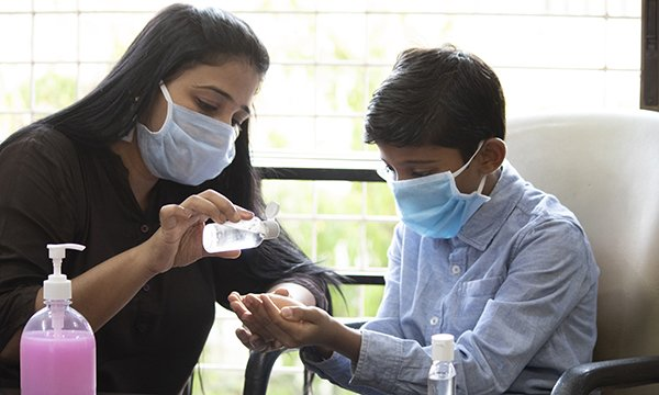 Picture of a woman showing a boy how to clean his hands with sanitiser. Both are wearing masks.