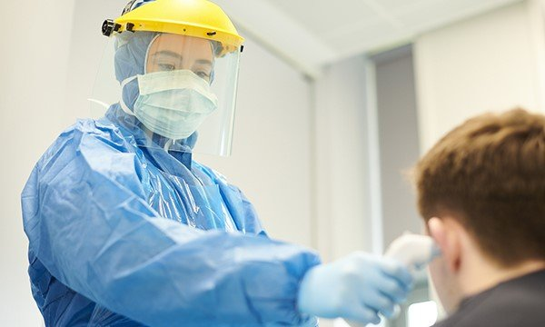 Picture shows a medic in protective clothing checking a boy's temperature. NICE is reviewing its critical care scale amid concerns that people with learning disabilities could be denied intensive care.
