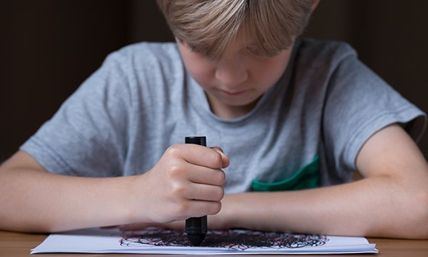 Boy drawing as part of therapy. School nurses, health visitors, and general practice nurses are often in a position to identify the damage due to trauma from adverse childhood experiences and the effect on children's mental health.