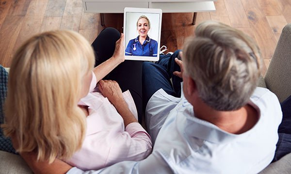 A man and a woman sitting on a sofa talking to a nurse via a video phone app