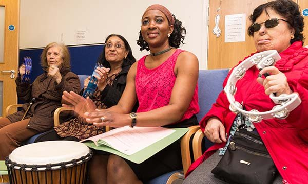 Picture shows two people playing drums and cymbals while others look on at a specialist dementia day care centre in London for people with moderate to severe dementia.