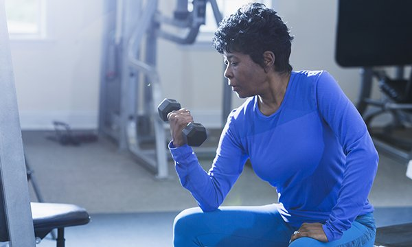 Picture shows a black woman in her 50s doing exercises in a gym. This article reports on advice from health professionals on how cancer nurses can support patients with the menopause.