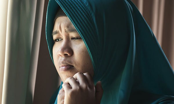 Picture shows a young woman wearing a hijab looking worried. A study shows women from ethnic minority backgrounds living in England are more likely to be embarrassed to go to their GP with potential cancer symptoms than white women