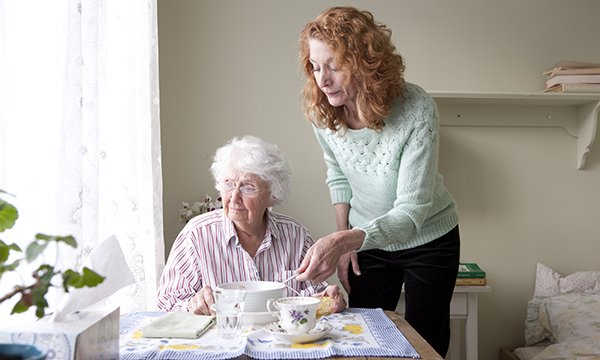 middle-aged woman helps older women with breakfast