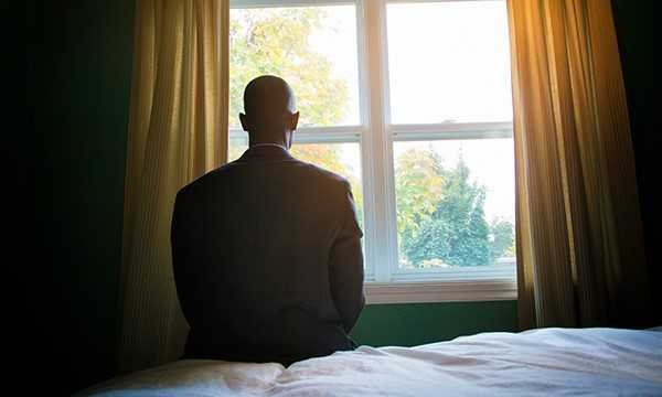 Silhouette of man sitting on bed, looking out window