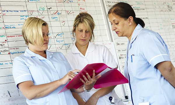 nurses confer in front of whiteboard