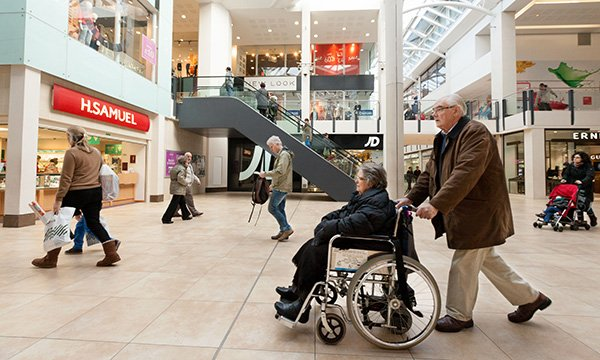 woman in wheelchair being pushed through shopping centre by man