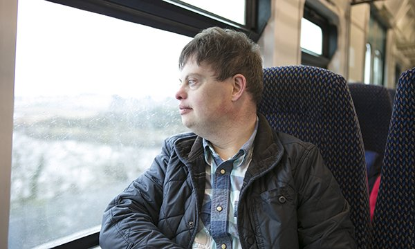 Image of a man with Down's syndrome looking out of a train window. Clare Taylor of mental health and learning disability at the charity Turning Point, talks about how to fix the system of care for people with learning disabilities and autism.