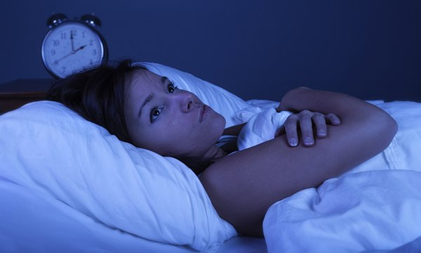 Picture shows a young woman suffering from insomnia with blue nighttime effect. This research digest looks at three studies relating to sleep health, insomnia and cognitive behavioural therapy as a primary care intervention.