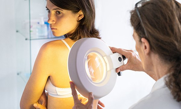 Picture shows a doctor examining the skin of a woman in her twenties. Melanoma rates for people aged 25-49 have risen 70% since the 1990s, but many cases could be prevented by using sunscreen.