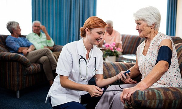 Community nurse visiting a female resident in a care home