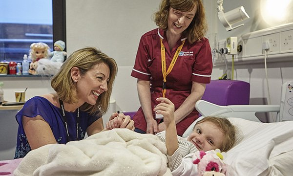 A Roald Dahl specialist children's nurse with a patient and another healthcare team member